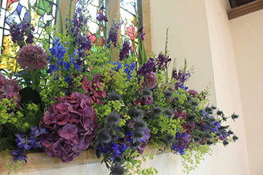 Purple and blue Summer flowers in church window
